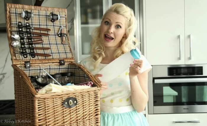 Abbey Sharp packing a picnic basket, holding a bottle.