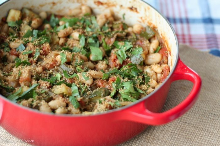 vegan cassoulet with white beans served in a large red casserole dish
