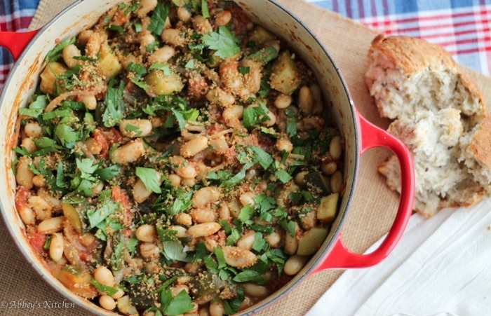vegan white bean cassoulet in a red pot garnished with parsley