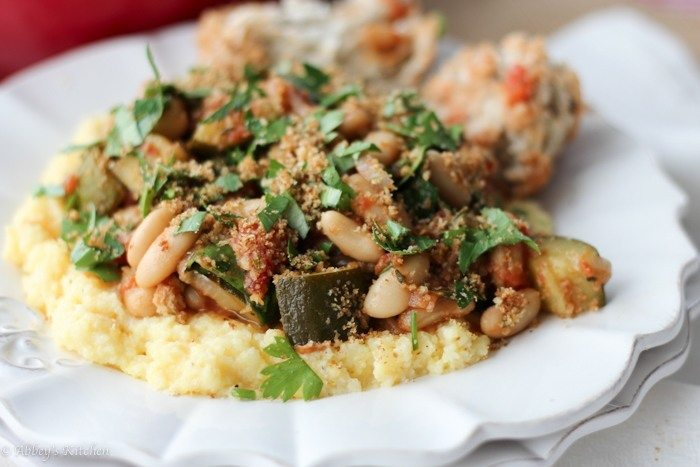 close up of vegan cassoulet with white beans and garlic breadcrumbs served on polenta garnished with fresh herbs