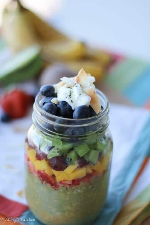 close up of vegan matcha overnight oatmeal in a clear jar garnished with fresh fruit, yogurt, and coconut flakes