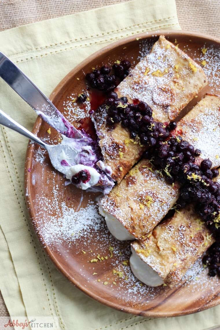 An overhead photo of plate of cheesecake stuffed french toast crepes with a knife and fork cutting into it.