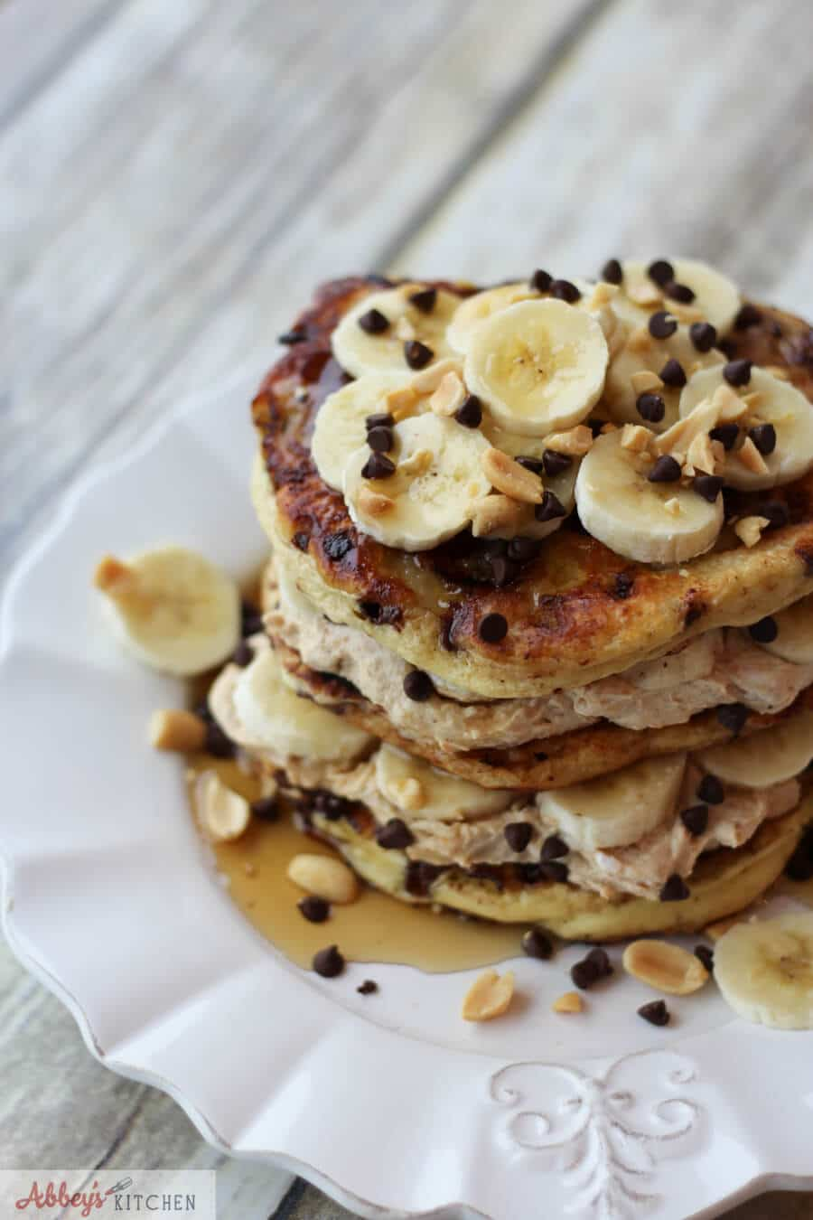 A stack of peanut butter banana protein pancakes with banana slices on top.
