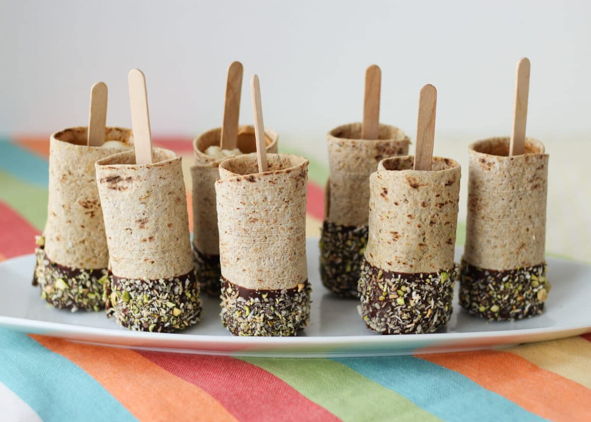 Photo of a plate of multiple vegan chocolate dipped banana roll ups on a stick.