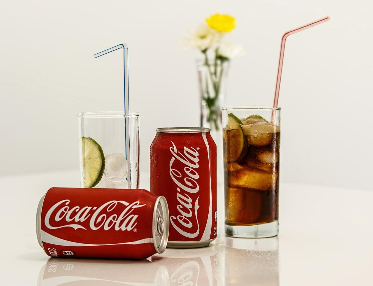 Two cans of coca cola beside two glasses with straws.