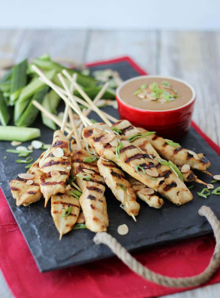 An image of a serving platter of multiple chicken satay with thai almond sauce in the background.