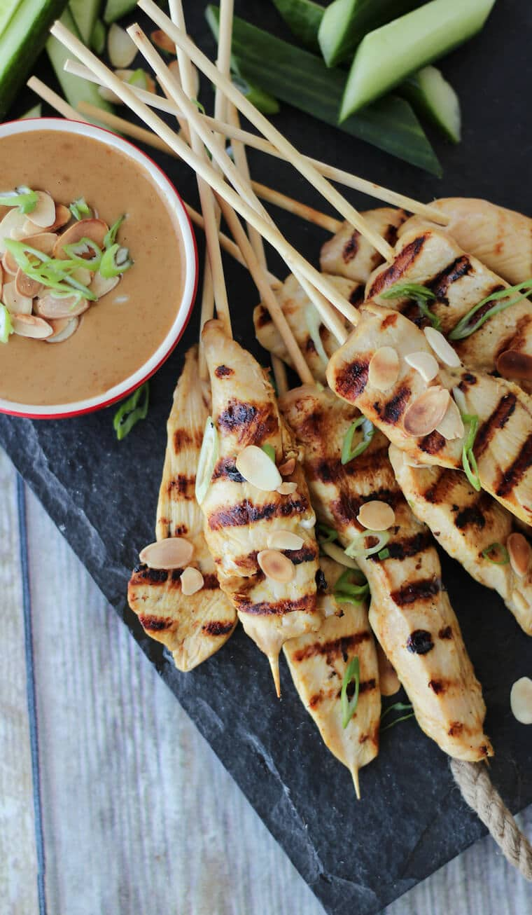 An overhead image of a serving platter of multiple chicken satay with thai almond sauce in the background.