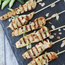 Overhead image of six gluten free chicken satay skewers with green onions on top.