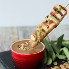 A skewer of chicken satay being dipped in an almond sauce.