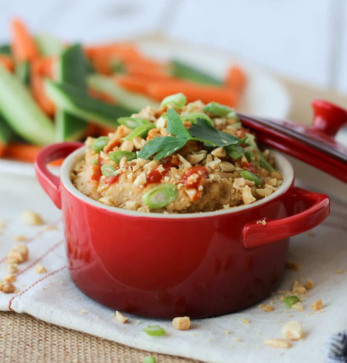 A red bowl of peanut hummus dip with sliced vegetables in the background.