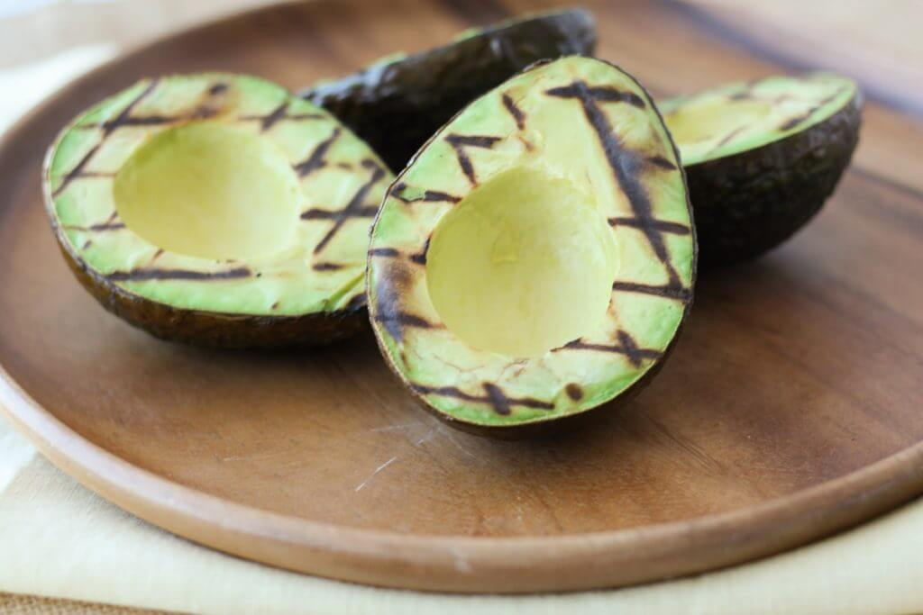 grilled avocado on a wooden plate