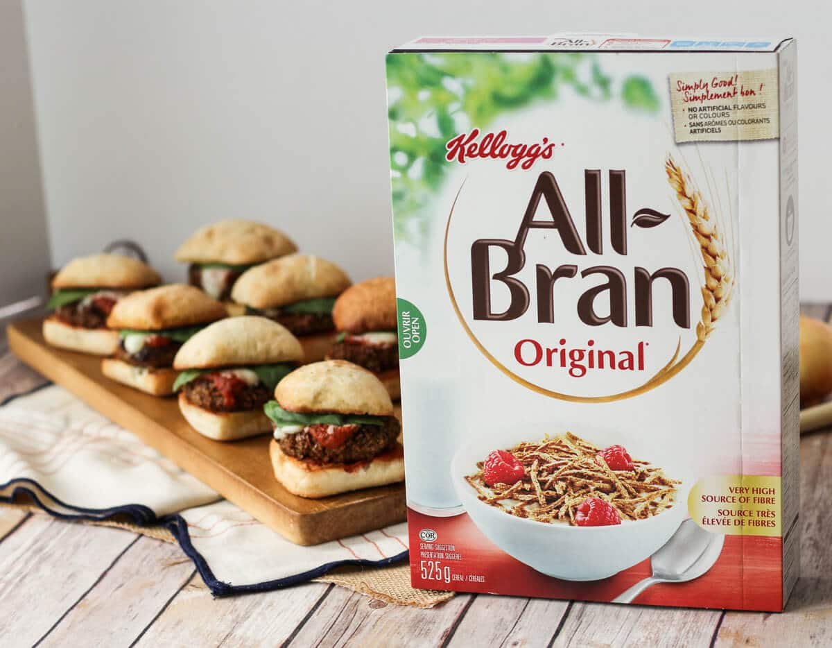 A box of All-Bran cereal in front of chicken sliders in the background.