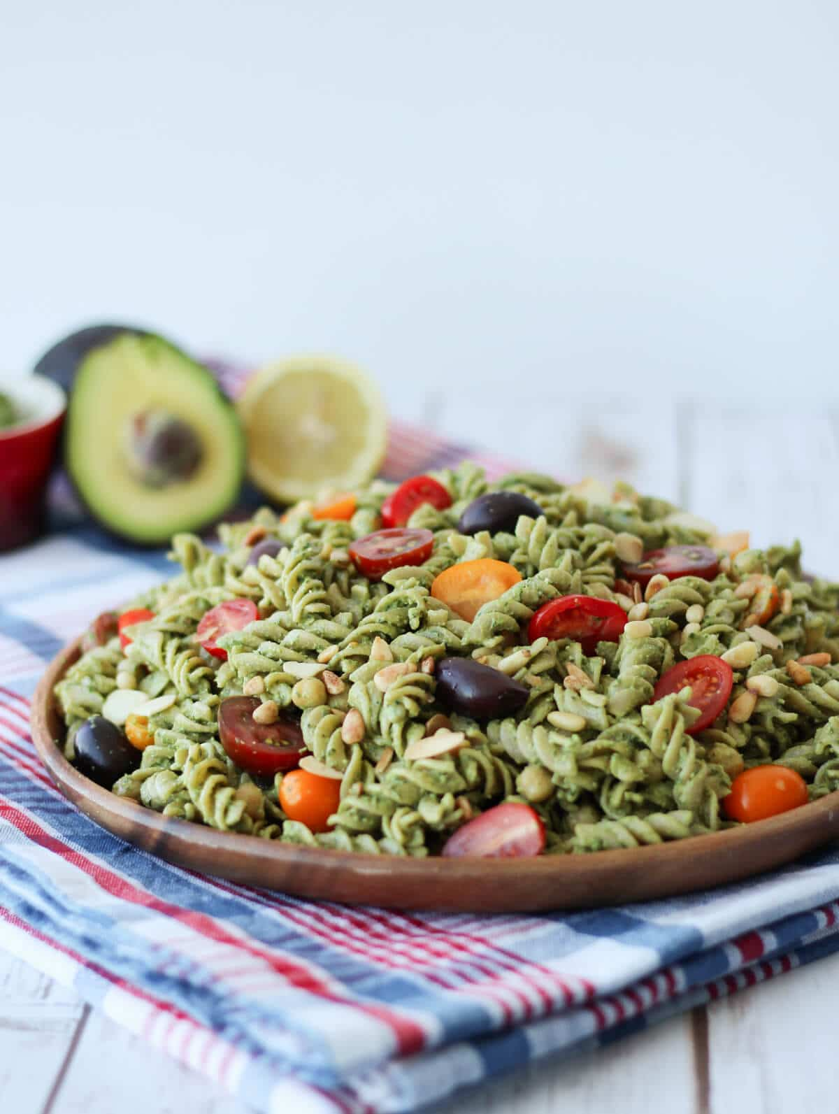 image of green vegan pesto salad with cherry tomatoes on a wooden dish with fresh avocado in the background