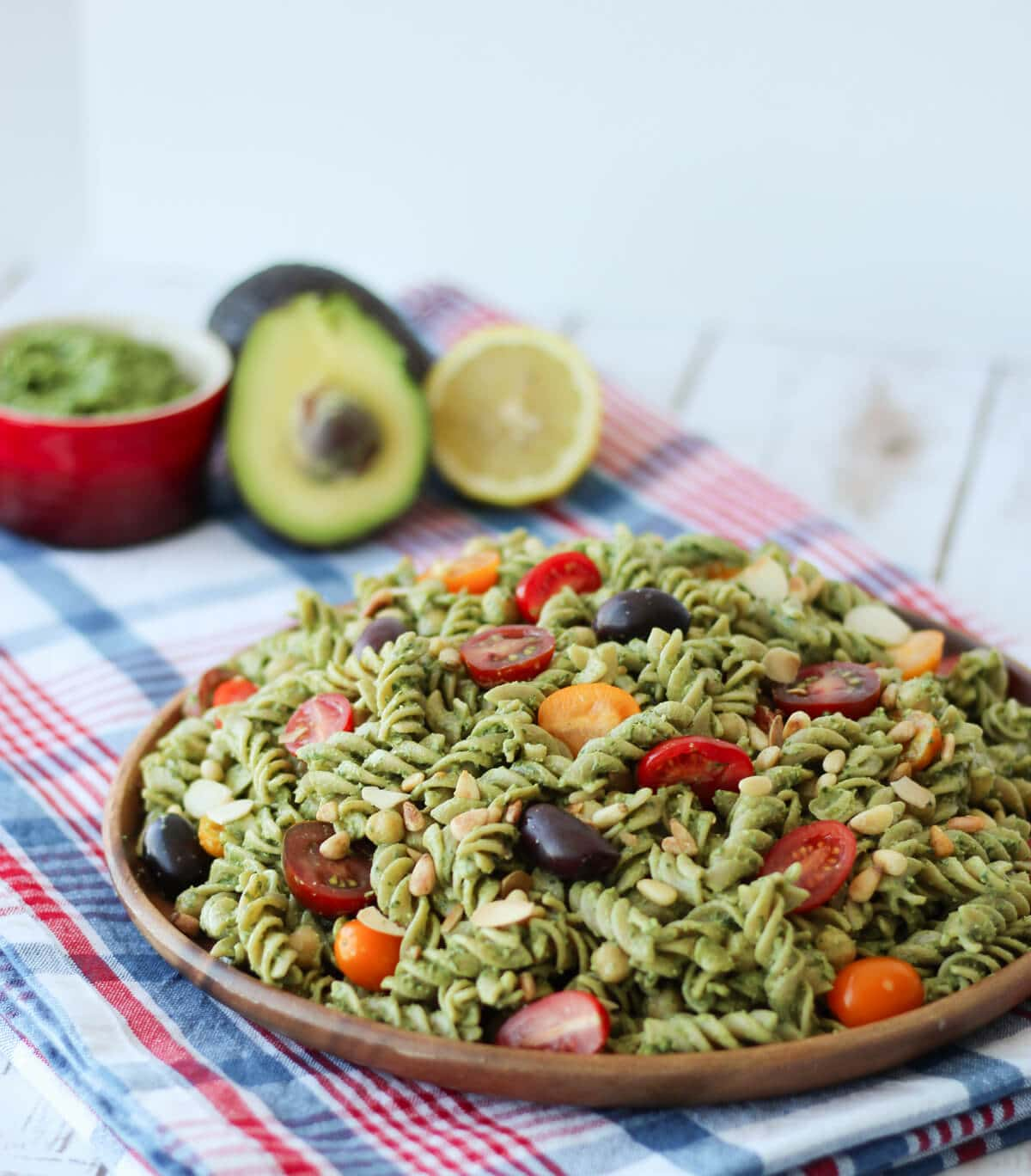 A wooden plate with pesto salad with sliced tomatoes.