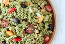 An overhead photo of a vegan pesto pasta salad on a wooden plate.