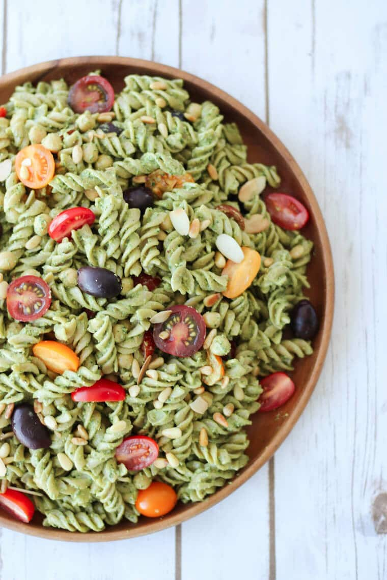 Pesto pasta salad with tomatoes and olives in a wooden bowl.