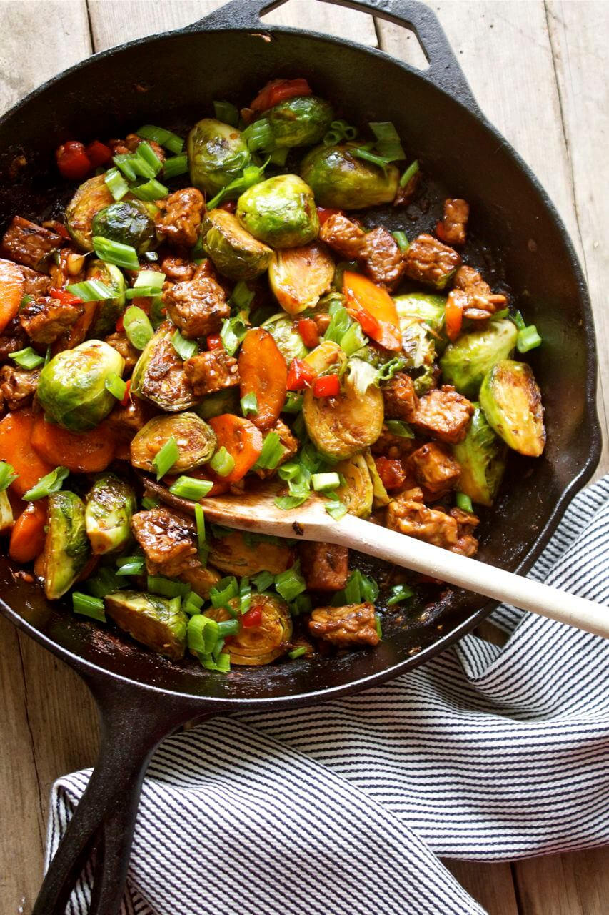 A pan with Brussels sprouts and tempeh stir fry with a spoon inside.