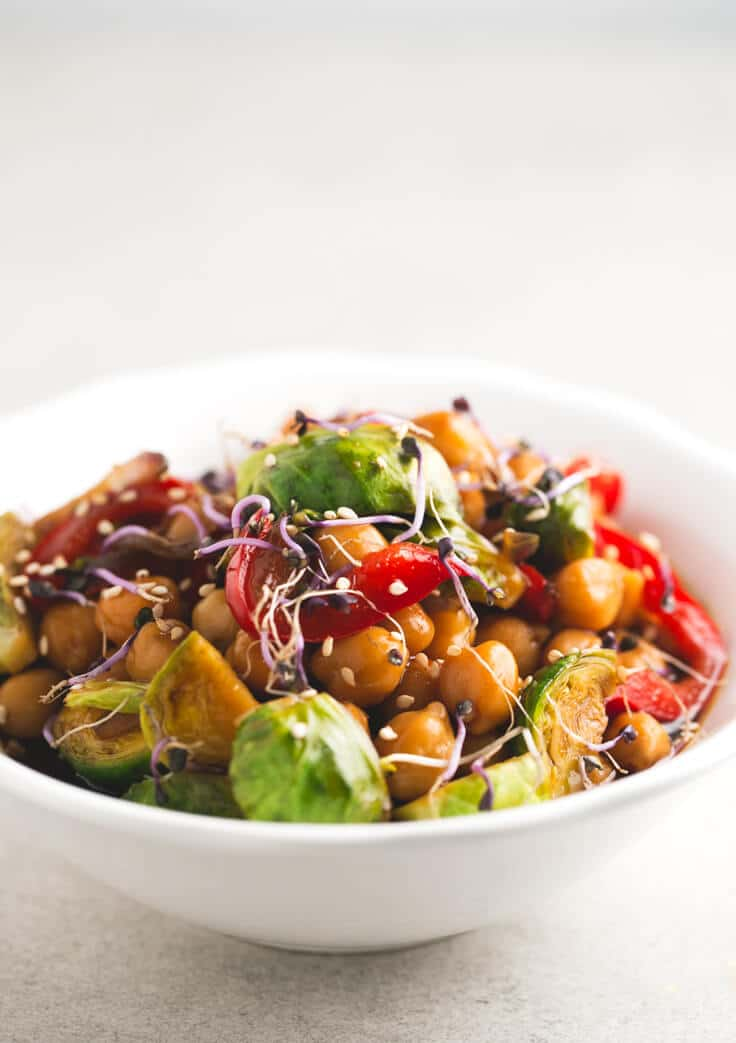 A white bowl with chickpea and vegetable stir fry.
