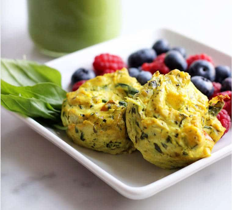 A plate with egg muffins and fruit.