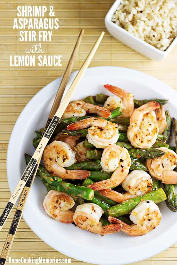A white plate with shrimp and asparagus stir fry with lemon sauce.