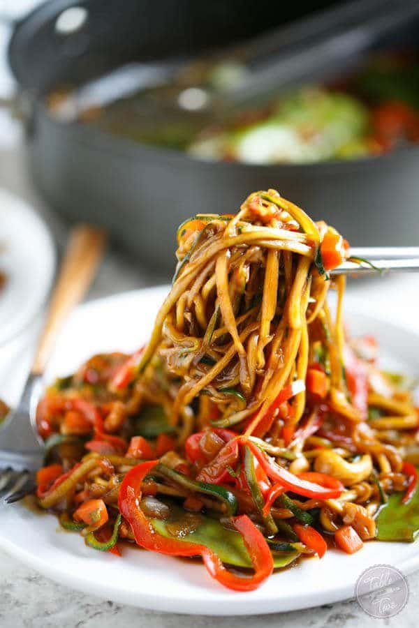 A plate with a cashew stir fry made with zoodles.