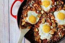 A shakshuka in a skillet with a wooden spoon scooping in.