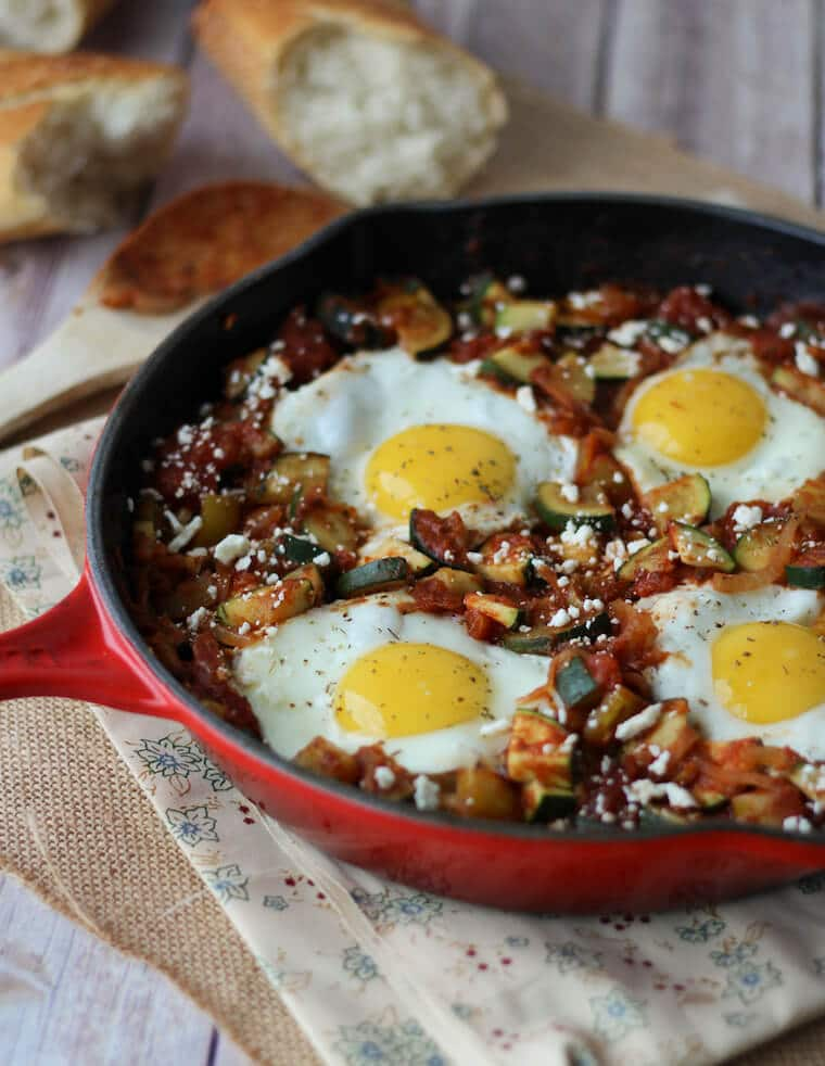 A red skillet containing a gluten free shaksuka with zucchini and feta.