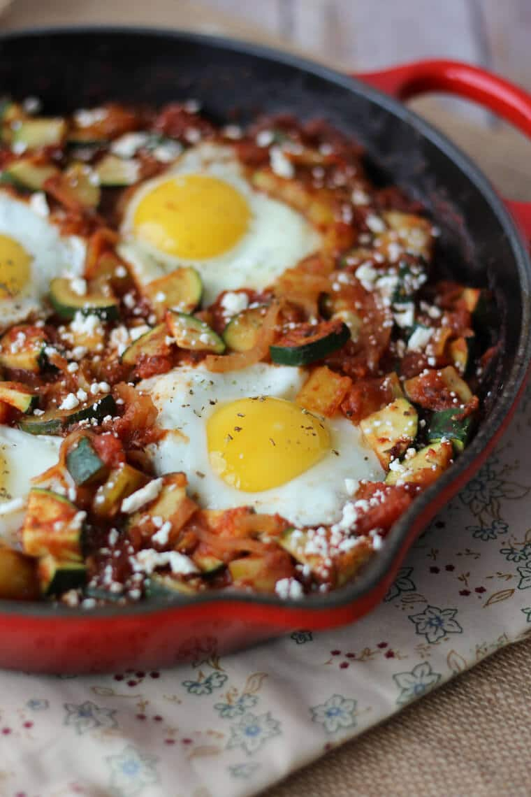 A close up photo of a red skillet containing a gluten free shaksuka with zucchini and feta.