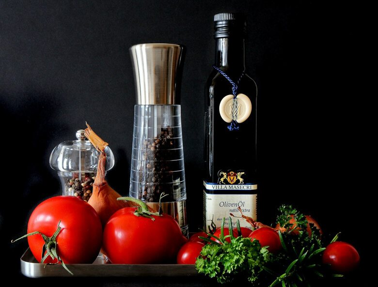 A table with a bottle of olive oil and a black pepper grinder with some fruit in front.