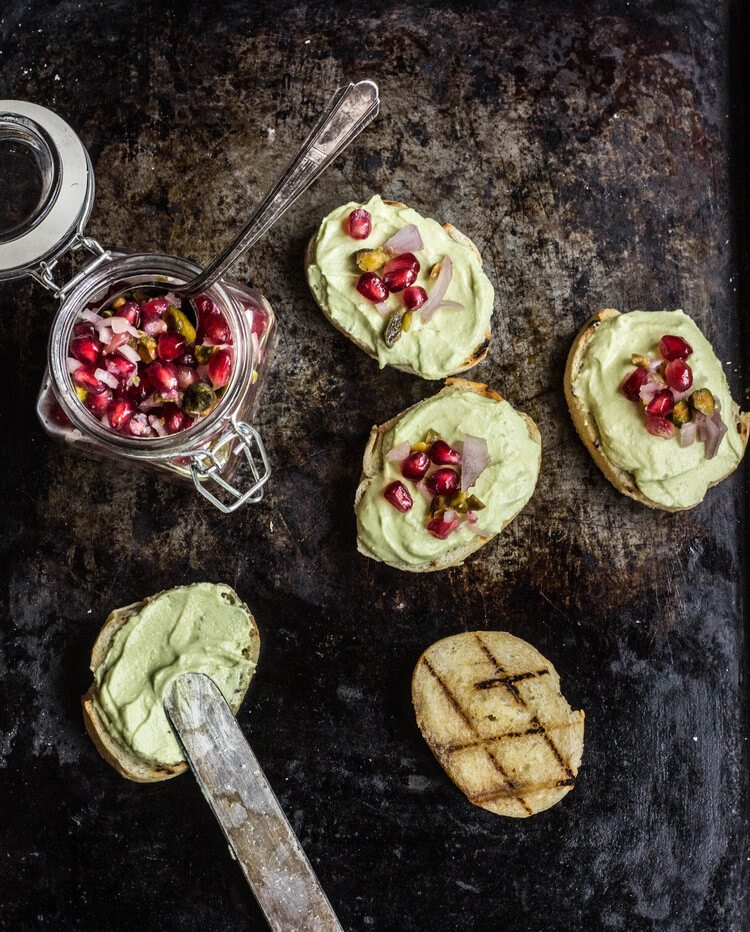 Overhead photo of five avocado toasts with pomegranate seeds on top.