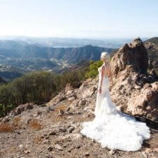 A view of a rocky mountain with Abbey Sharp in a wedding dress standing in front.