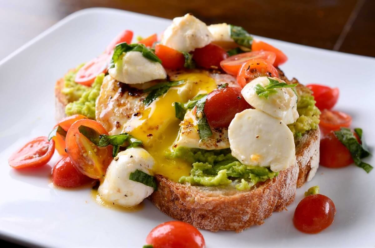 A white plate with avocado toast with caprese.