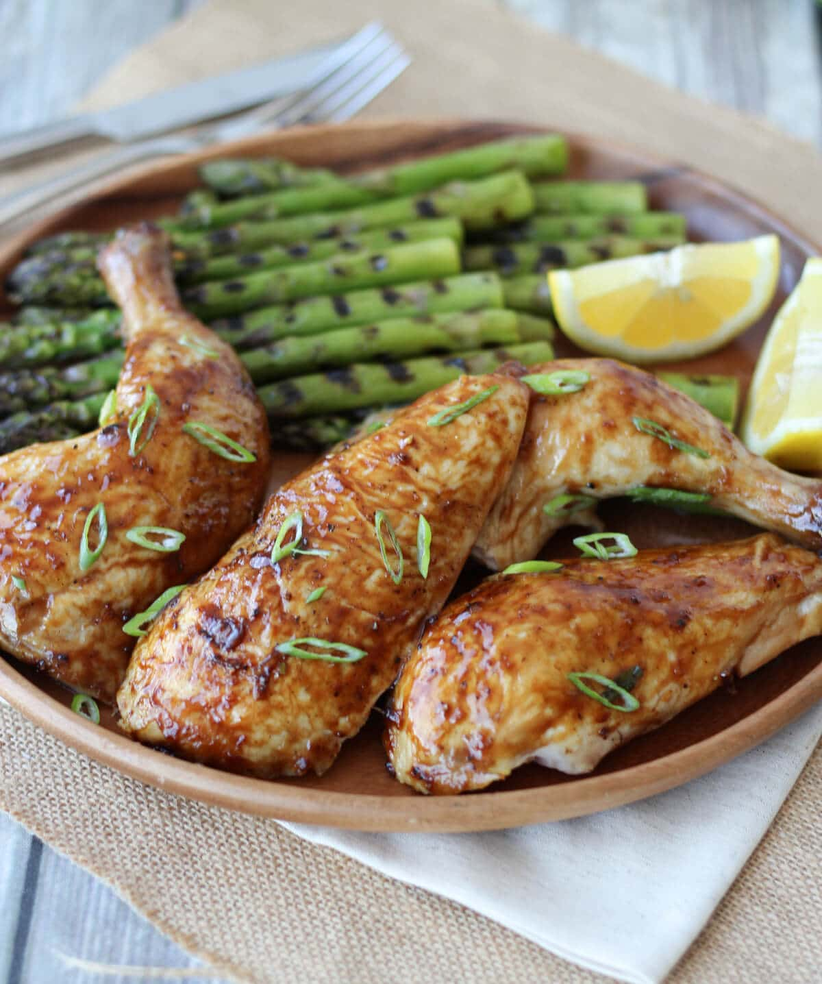 A brown plate with chicken and grilled asparagus.