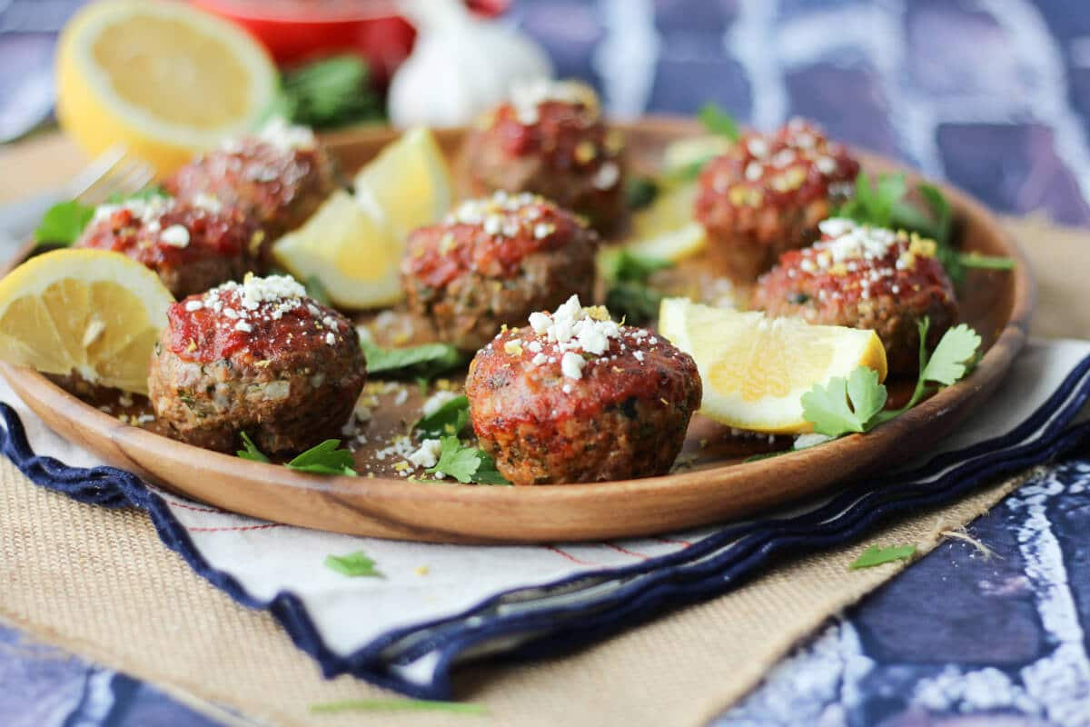 medium long shot of a wooden plate containing greek freezer meatloaf muffins garnished with fresh greens, lemon wedges, and feta cheese against a blue tile wall