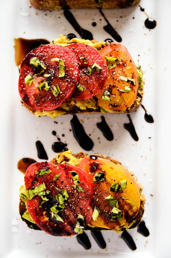 Avocado toast with slices of tomatoes on top with balsamic on top.
