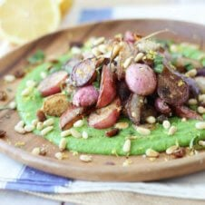 A close up of a plate of za'atar roasted radishes over top of a pea puree.