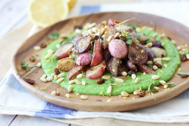 A close up of a plate of za\'atar roasted radishes over top of a pea puree.