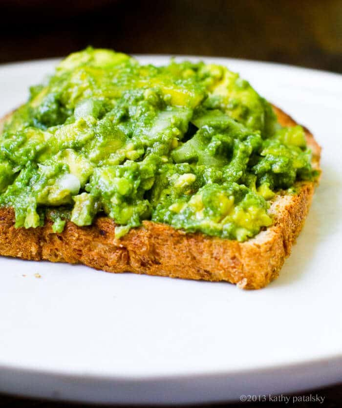 A close up of mashed avocado on toast.