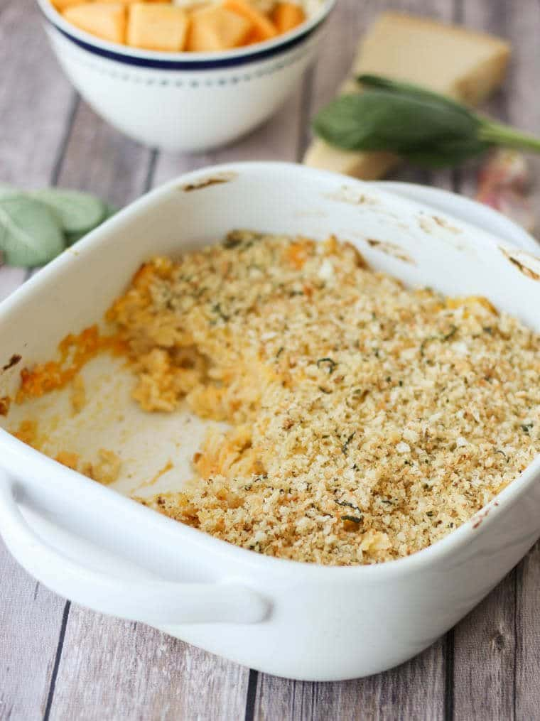 butternut squash and cauliflower mac and cheese in a white casserole dish garnished with sage
