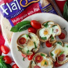 A plate of egg cups with tomatoes and basil with a package of flatout flatbread behind it.