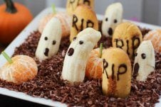 An edible graveyard made with bananas with ghost faces.