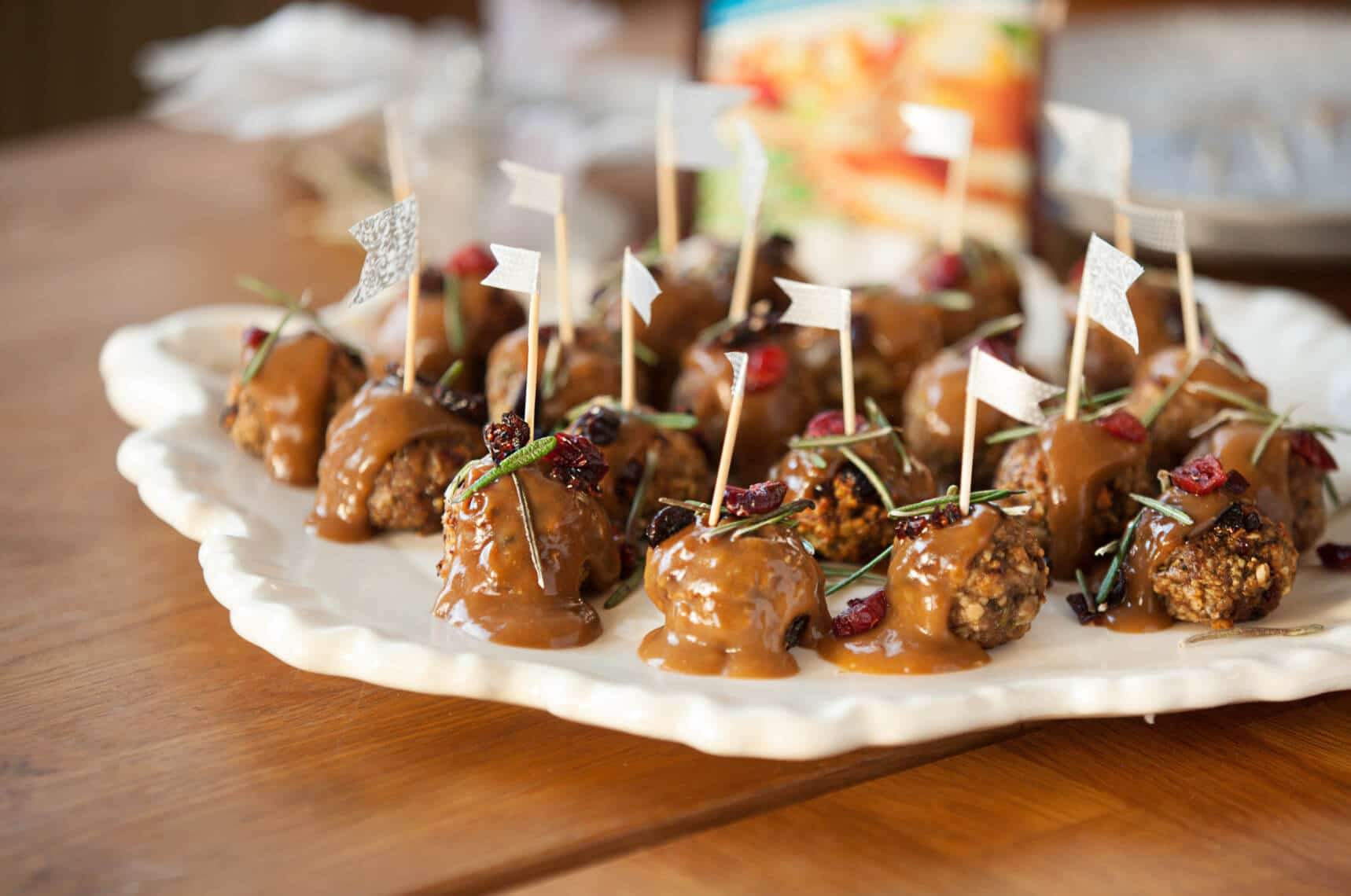 several cranberry flavoured meatballs on a white decorative plate