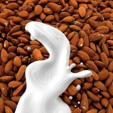 Almonds with milk splashed in front.
