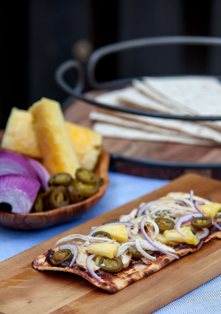 A photo of a grilled pizza using flat bread topped with pineapple, onions, and jalapeno.