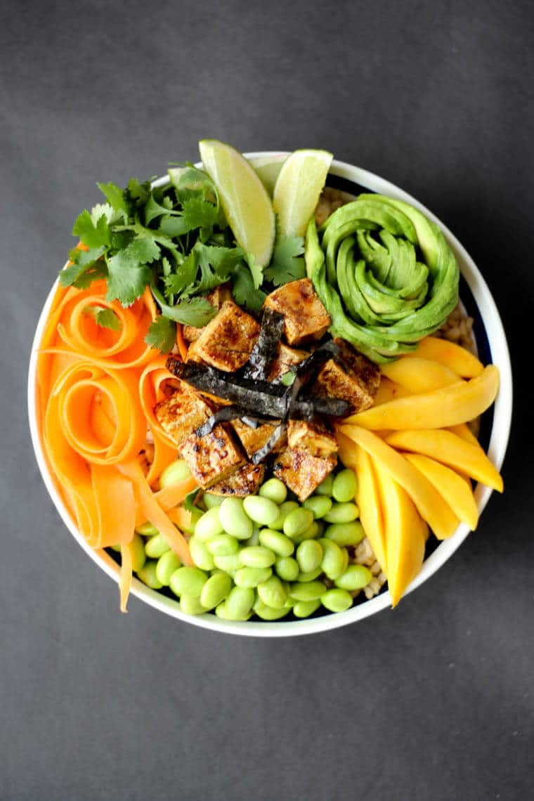An overhead image of a poke bowl with crispy tofu, carrots, avocado, beans, lime, and cilantro.