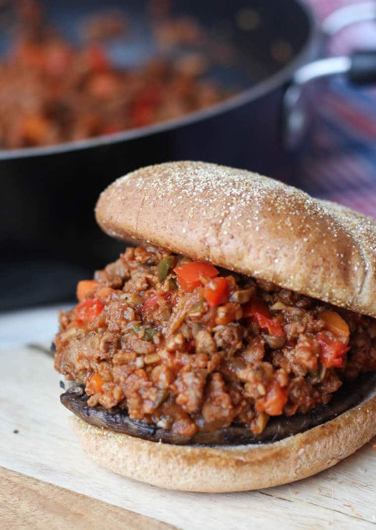 An opened sandwich with vegan sloppy joes on a wooden serving board.