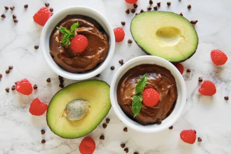 An overhead photo of two bowls of chocolate raspberry avocado pudding with avocados around it.