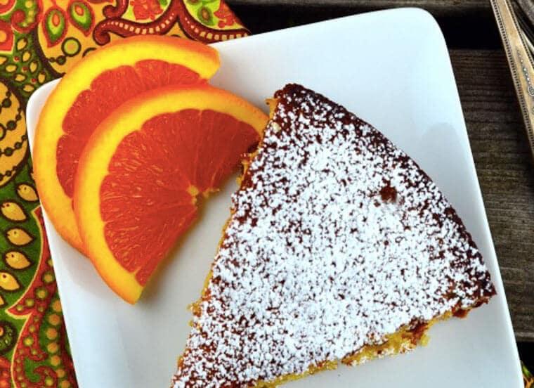 A slice of orange almond honey cake on a plate.