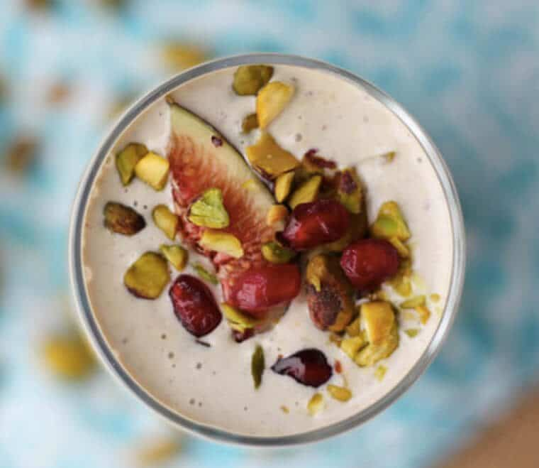birds eye view of pistachio tahini smoothie in a clear glass garnished with fruit and pistachios