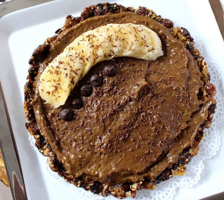 An overhead photo of a vegan chocolate banana pudding pie with sliced bananas on top.
